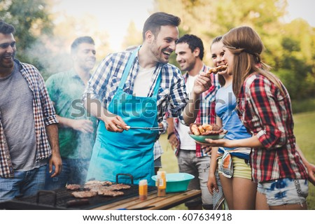 Friends having a barbecue party in nature  while having a blast