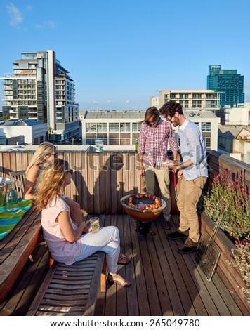Friends having a barbeque on the outdoor rooftop terrace with skewer kebabs - stock photo