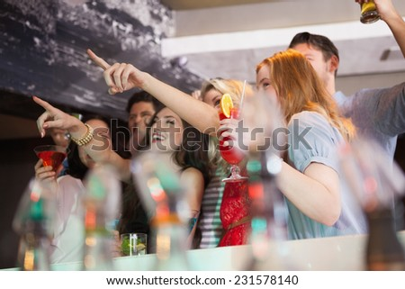 Friends having a drink together and pointing something in a bar - stock photo
