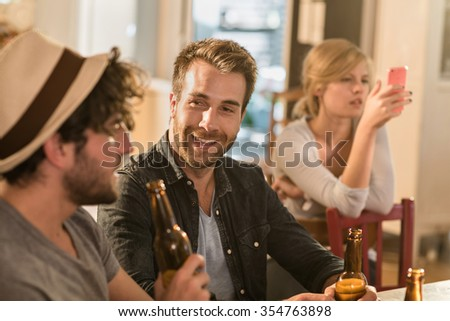 Friends having a drinks on a sunny evening in a cozy house. Two men are sitting at a table with beers, a blonde girl is looking at her phone in the back. They are wearing casual clothes - stock photo