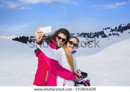 friends having a selfie on the snow - stock photo