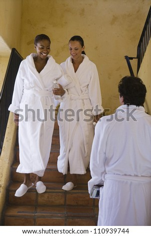 Friends having conversation on staircase at resort - stock photo