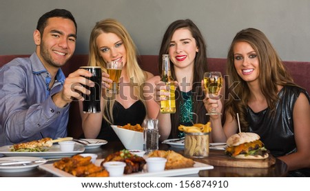Friends having dinner together smiling at camera at the restaurant - stock photo