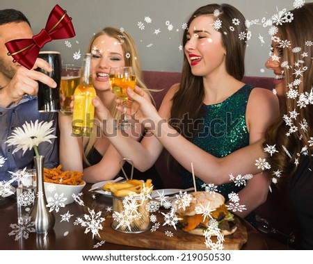 Friends having dinner together with digitally generated red shiny bow - stock photo