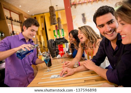 Friends having drinks at the bar looking very happy - stock photo