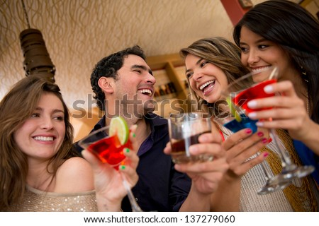 Friends having drinks at the club looking very happy - stock photo
