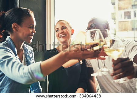 Friends having fun at a local bar while drinking white wine and laughing - stock photo