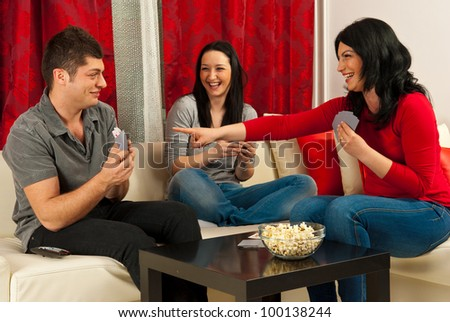 Friends having fun at playing cards game,one of women  laughing and pointing to man accusing he cheated - stock photo
