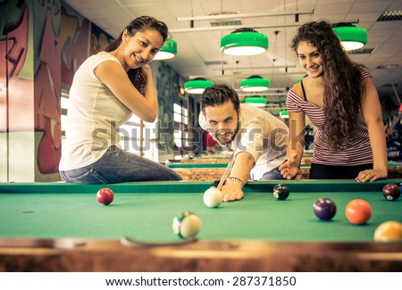 friends having fun at the pool arcade room. three friends playing together. - stock photo