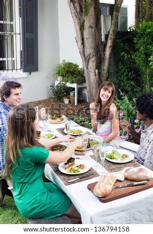 Friends having fun, talking and laughing at a party with food and alcohol, a casual lunch get together in a garden - stock photo