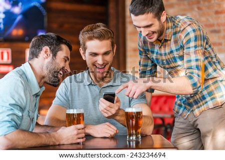 Friends having fun. Three happy young men in casual wear drinking beer in pub while one of them pointing smart phone and smiling  - stock photo