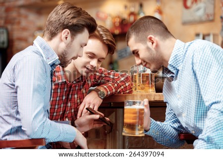 Friends having fun. Three happy young men in casual wear drinking beer in pub while one of them showing screen of his smart phone  - stock photo
