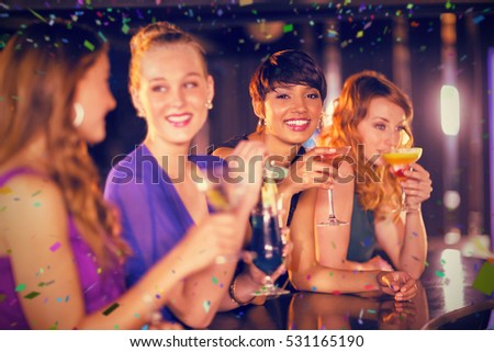 Friends having glass of cocktail in bar against flying colours