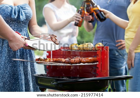 Friends having party with barbecue in a garden - stock photo