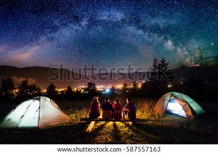Friends hikers sitting on a bench made of logs and watching fire together beside c& and & Camping Stock Images Royalty-Free Images u0026 Vectors | Shutterstock