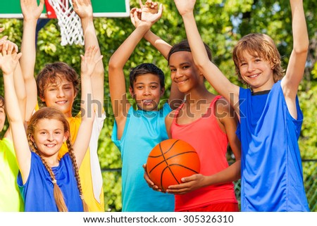 Friends hold arms up at basketball game - stock photo