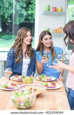 Friends holding glass of wine while having meal at home