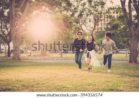 Friends holding hands when running in city park - stock photo