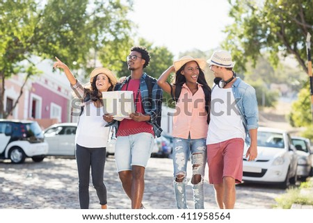 Friends holding map and pointing outdoors - stock photo