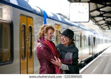 Friends hugging at a train station - stock photo