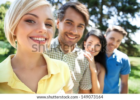 Friends in a row. Young cheerful people standing in a row and smiling - stock photo