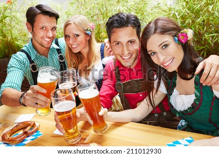 Friends in bavaria clinking beer glasses in summer in a beer garden - stock photo