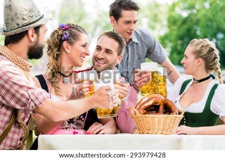 Friends in Bavarian beer garden drinking in summer - stock photo