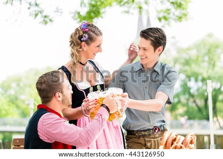 Friends in beer garden clinking glasses with beer, pretzel standing on the table - stock photo