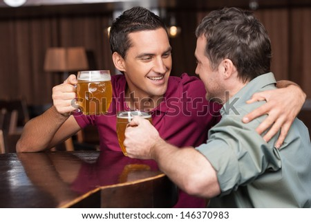 Friends in beer pub. Two cheerful friends drinking beer and talking at bar