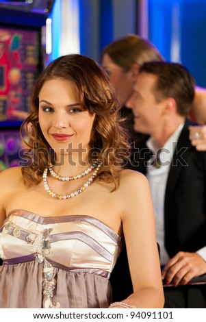 Friends in Casino on a slot machine; a woman is looking into the camera - stock photo
