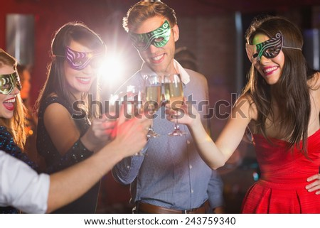 Friends in masquerade masks toasting with champagne at the nightclub - stock photo