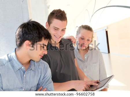 Friends in school corridor using electronic tablet - stock photo