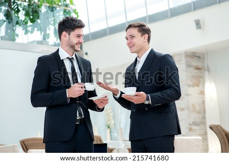 Friends in the business. Two other businessman drinking coffee and talking to each other while standing in an office and smiling to each other