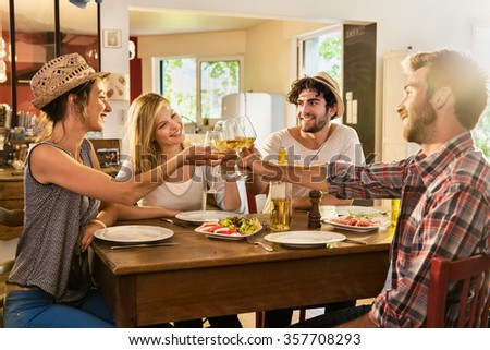 Friends in their 30's having a nice aperitif on a rustic wooden table in a lovely house. They are having fun and talking in front of glasses of white wine and tomatoes mozzarella - real people