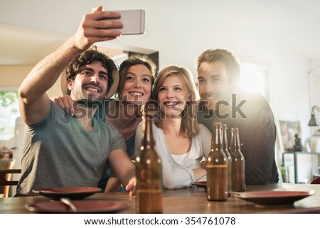 Friends in their 30's taking selfies on a smartphone in a charming house. Two men and two women are smiling while the phone is taking the picture. Backlit shot with flare, real people. - stock photo