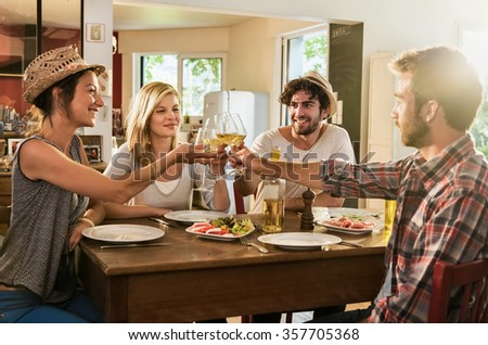 Friends in their thirties having a nice aperitif on a rustic wooden table in a lovely house. They are holding their high glasses of white wine. There are tomatoes mozzarella for starters. - stock photo