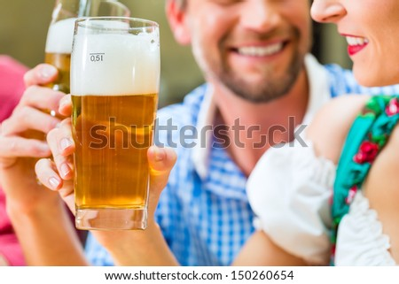 Friends in traditional Bavarian Tracht in restaurant or pub with beer - stock photo