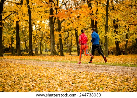 Friends jogging together in park - beautiful autumn season - stock photo
