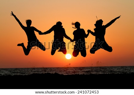 friends jumping in sunset at beach