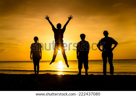 friends jumping in sunset at the beachside