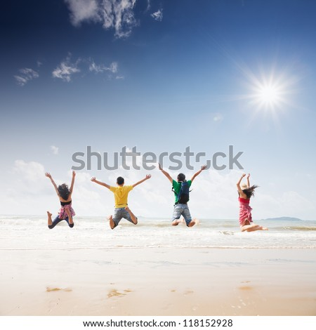 friends jumping on beach - stock photo