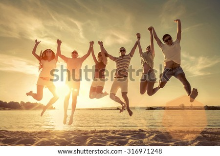 Friends jumping on the beach under sunset sunlight. - stock photo