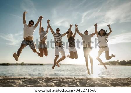 Friends jumping on the beach under sunset sunlight. - stock photo