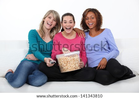 Friends laughing and eating popcorn - stock photo