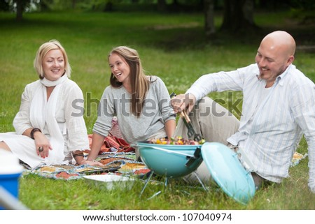 Friends laughing and having fun in park eating barbecue - stock photo