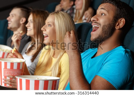 Friends laughing during a movie while eating popcorn - stock photo