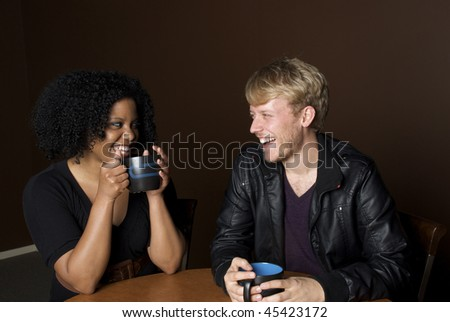 Friends laughing over a cup of coffee - stock photo