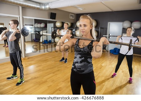 Friends Lifting Barbells While Standing In Health Club - stock photo