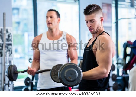 Friends lifting weights for sport in fitness gym motivating each other with a little competition