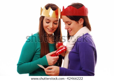 Friends looking at joke from christmas cracker on white background - stock photo